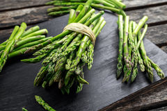 Fresh raw green Asparagus on wooden chopping board.  Stock Photos