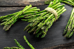 Fresh raw green Asparagus on wooden chopping board.  Royalty Free Stock Photos