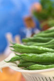 Fresh Raw Green Beans. Sprinkled with water in white plastic strainer (Selective Focus, Focus on the bean one third into the strainer Stock Photos