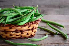Fresh raw green beans in a brown basket and on a vintage wooden table. Young beans pods photo. Green string beans crop. Fresh raw green beans. Young beans pods Stock Photo