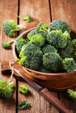Fresh raw green broccoli in bowl. On rustic wooden background Royalty Free Stock Photos