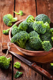 Fresh raw green broccoli in bowl. On rustic wooden background Royalty Free Stock Image