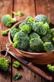 Fresh raw green broccoli in bowl. On rustic wooden background Royalty Free Stock Images