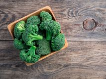 Fresh raw green broccoli in wooden bowl on wooden background, to. P view Stock Photography