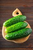 Fresh raw green cucumbers on a wooden table. Fresh raw green cucumbers on a wooden table Royalty Free Stock Images