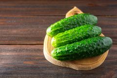 Fresh raw green cucumbers on a wooden table. Fresh raw green cucumbers on a wooden table Royalty Free Stock Photos