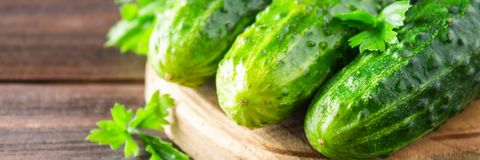 Fresh raw green cucumbers on a wooden table. Banner. Fresh raw green cucumbers on a wooden table Stock Photos