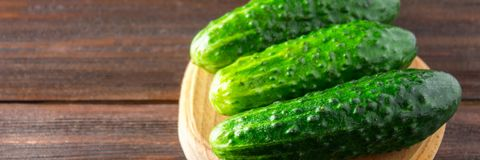 Fresh raw green cucumbers on a wooden table banner. Fresh raw green cucumbers on a wooden table Stock Images