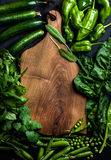 Fresh raw green ingredients for healthy cooking or salad making with dark wooden cutting baoard in center, top view. Fresh raw green vegetable ingredients for Royalty Free Stock Image