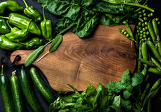 Fresh raw green ingredients for healthy cooking or salad making with dark wooden cutting baoard in center, top view Royalty Free Stock Photo