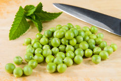 Fresh raw green peas. On wooden chopping board, with mint and kitchen knife Stock Images
