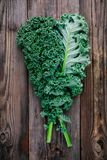 Fresh raw green superfood kale curly cabbage leaves. On wooden background Royalty Free Stock Photos