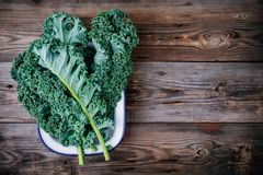 Fresh raw green superfood kale curly cabbage leaves. On wooden background Royalty Free Stock Images