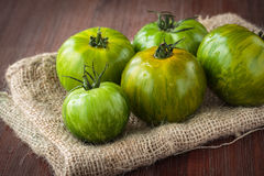 Fresh raw green tomatoes. Delicious fresh raw green tomatoes for an healthy nutrition Stock Photo