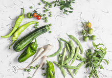 Fresh raw green vegetables - zucchini, green peas and beans, parsnips, peppers, tomatoes, onions on a white background. Healthy  Vegetarian, vegan table Stock Images