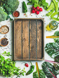 Fresh greens, vegetables and grains with wooden box in center. Fresh raw greens, unprocessed vegetables and grains over light grey marble kitchen countertop Stock Image