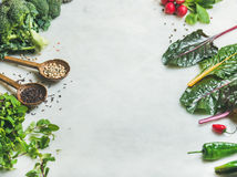 Fresh raw greens, vegetables and grains over marble countertop. Fresh raw greens, unprocessed vegetables and grains over light grey marble kitchen countertop Stock Image
