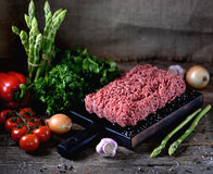 Fresh raw ground beef with fresh vegetables on an old wooden background. Rustic style. Food Royalty Free Stock Images