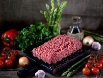 Fresh raw ground beef with fresh vegetables on an old wooden background. Rustic style. Food Royalty Free Stock Photos