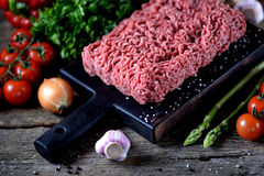 Fresh raw ground beef with fresh vegetables on an old wooden background. Rustic style. Food Stock Photography