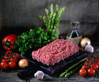 Fresh raw ground beef with fresh vegetables on an old wooden background. Rustic style. Food Royalty Free Stock Photo