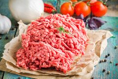 Fresh raw ground beef on a paper. On a rustic wooden table Stock Photo