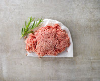 Fresh raw ground meat. On white wrapping paper on gray kitchen table Stock Images