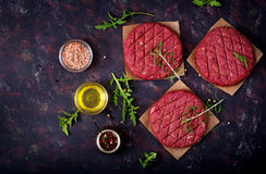 Fresh raw homemade minced beef steak burger with spices. On black background Stock Photo