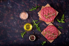 Fresh raw homemade minced beef steak burger with spices. On black background Royalty Free Stock Photos