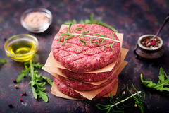 Fresh raw homemade minced beef steak burger with spices. On black background Stock Photos