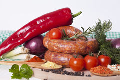 Fresh raw homemade sausage with spices and vegetables on a white. Background. Sausage for cooking and baking with pepper, onion, cherry, dill and various spices Royalty Free Stock Photos
