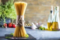 Fresh raw homemade spaghetti PASTA on Dark Table. stock image