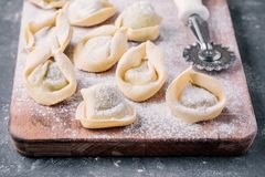 Fresh raw homemade tortellini or ravioli pasta closeup. Fresh raw homemade tortellini or ravioli pasta on dark background closeup Royalty Free Stock Photo