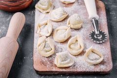 Fresh raw homemade tortellini or ravioli pasta. On dark background Stock Images