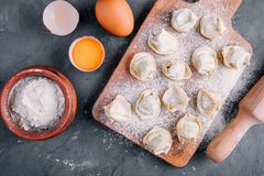 Fresh raw homemade tortellini or ravioli pasta. On dark background Royalty Free Stock Images