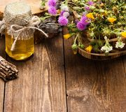 Fresh, raw honey and wild flowers. Bottle filled with fresh, raw honey and bouquet of wildflowers in ligneous basket on wooden planks Royalty Free Stock Photo