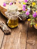 Fresh raw honey and wild flowers. Bottle filled with fresh, raw honey and bouquet of wildflowers in ligneous basket on wooden planks Stock Photography