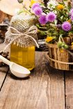 Fresh, raw honey and wild flowers. Bottle filled with fresh, raw honey, wooden spoon, bouquet of wildflowers in ligneous basket on wooden planks Royalty Free Stock Photos
