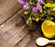 Fresh, raw honey and wild flowers. Ceramic cup filled with fresh, raw honey, wooden spoon, bouquet of wildflowers in ligneous basket on wooden planks. Copy space Stock Photos