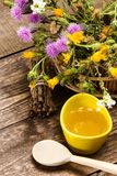 Fresh, raw honey and wild flowers. Ceramic cup filled with fresh, raw honey, wooden spoon, bouquet of wildflowers in ligneous basket on wooden planks Royalty Free Stock Image