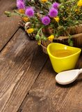 Fresh, raw honey and wild flowers. Ceramic cup filled with fresh, raw honey, wooden spoon, bouquet of wildflowers in ligneous basket on wooden planks. Copy space Royalty Free Stock Photos