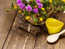 Fresh, raw honey and wild flowers. Ceramic cup filled with fresh, raw honey, wooden spoon, bouquet of wildflowers in ligneous basket on wooden planks. Copy space Stock Photo