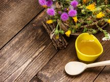 Fresh, raw honey and wild flowers. Ceramic cup filled with fresh, raw honey, wooden spoon, bouquet of wildflowers in ligneous basket on wooden planks. Copy space Royalty Free Stock Image