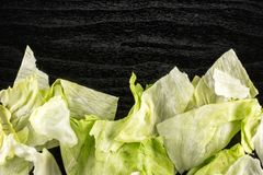 Fresh raw Iceberg Lettuce on black wood. Iceberg lettuce fresh torn salad leaves stack table top isolated on black wooden background Royalty Free Stock Photo