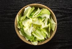 Fresh raw Iceberg Lettuce on black wood. Iceberg lettuce table top fresh torn salad leaves in a wooden bowl isolated on black wood background Royalty Free Stock Photography