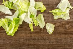 Fresh raw Iceberg Lettuce on brown wood. Iceberg lettuce fresh torn salad leaves stack table top isolated on brown wooden background Royalty Free Stock Photos