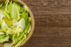 Fresh raw Iceberg Lettuce on brown wood. Iceberg lettuce fresh torn salad leaves in a wooden bowl table top isolated on brown wood background Stock Photos