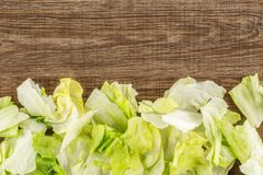 Fresh raw Iceberg Lettuce on brown wood. Iceberg lettuce fresh torn salad leaves stack table top isolated on brown wood background Stock Image