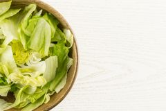 Fresh raw Iceberg Lettuce on grey wood. Iceberg lettuce fresh torn salad leaves in a wooden bowl table top isolated on grey wood background Stock Photography