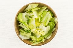 Fresh raw Iceberg Lettuce on grey wood. Iceberg lettuce table top fresh torn salad leaves in a wooden bowl isolated on grey wood background Royalty Free Stock Photos